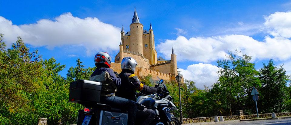 Ruta en moto por Castilla, con un castillo en el fondo