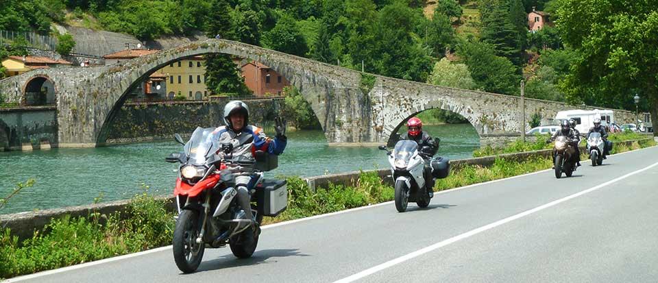 4 motos con un puente en el fondo durante una ruta hecha en moto en la Provenza y Toscana